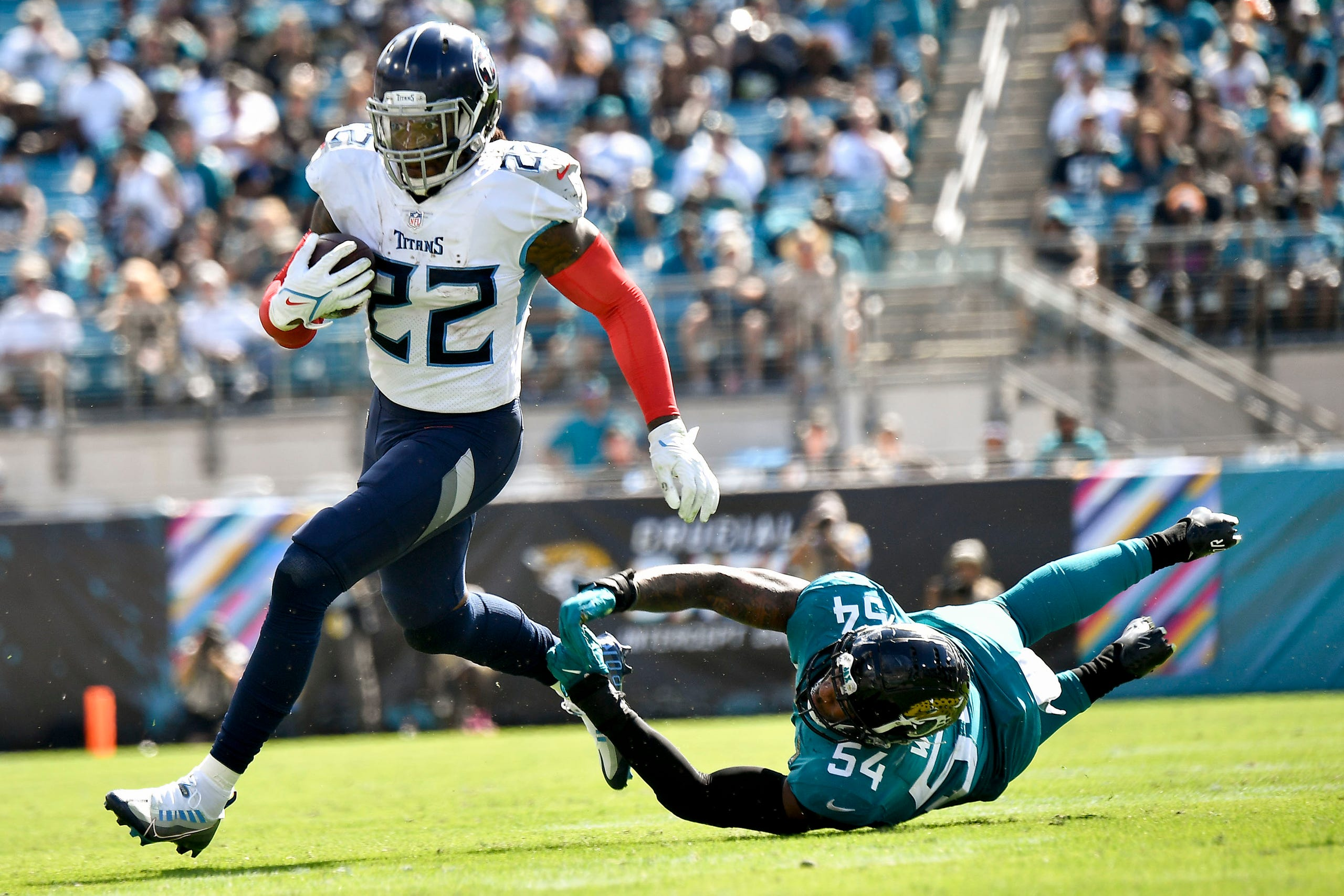 Tennessee Titans running back Derrick Henry (22) rushes for a first down under pressure from Jacksonville Jaguars middle linebacker Damien Wilson (54) during the third quarter of the game at TIAA Bank Field Sunday, Oct. 10, 2021 in Jacksonville, Fla.