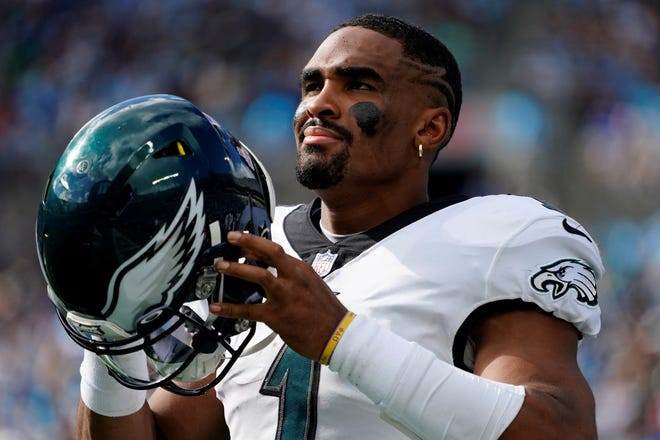 Philadelphia Eagles quarterback Jalen Hurts watches during the second half of an NFL football game against the Carolina Panthers Sunday, Oct. 10, 2021, in Charlotte, N.C. (AP Photo/Jacob Kupferman)