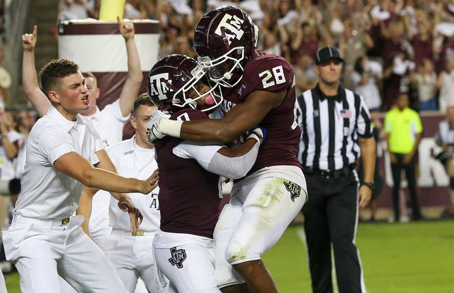 Texas A&M receiver Ainias Smith (0) celebrates his touchdown with Isaiah Spiller (28) in the first quarter against Alabama.
