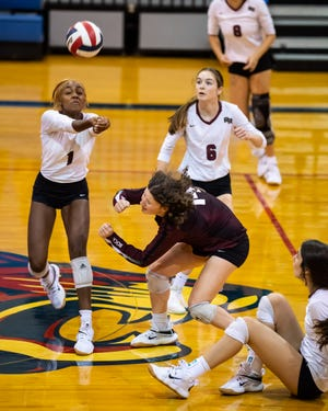 Lauryn Moore, left, passes the ball  in a win over Troy in August. Moore, one of 10 seniors on Round Rock's volleyball team, took advantage of extended playing time to fire 12 kills in a sweep of Hutto Friday.
