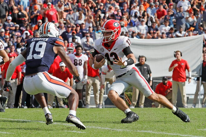Oct 9, 2021; Auburn, Alabama, USA;  Georgia Bulldogs quarterback Stetson Bennett (13) carries as Auburn safety Bydarrius Knighten (19) closes in during the second quarter at Jordan-Hare Stadium. John Reed-USA TODAY Sports