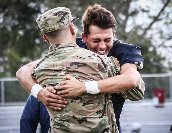 Eustis quarterback Blayne Romano hugs his older brother, Tanner, during Thursday's Senior Night celebration at the Panther Den in Eustis. Tanner, a former Eustis quarterback and currently an air traffic controller with the U.S. Air Force, surprised his brother by flying in from Oklahoma, where he is stationed. [COURTESY / ROBIN HAMEL]