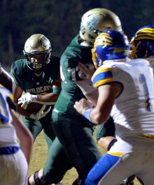 Eastern Randolph's Na'Hiem Lilly looks for running room as the Wildcats' Landon Loflin takes on two blockers against Southwestern Randolph. Lilly had three touchdowns in Eastern Randolph's 43-7 win over Trinity last week. [Mike Duprez/Courier-Tribune]