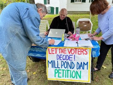Durham petitioners are working to preserve the Mill Pond dam on the Oyster River. Behind the table is Larry Harris and at left is Stephen Burns. The woman at right is not identified.