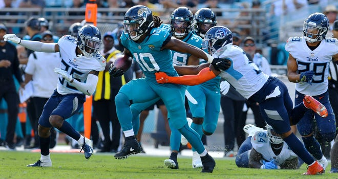 Jaguars wide receiver Laviska Shenault Jr. (10) breaks away from Titans defensive linemen on his way to a long first down run to the 12 yard line during fourth quarter action Sunday against Titans.Bob Self/Florida Times-Union