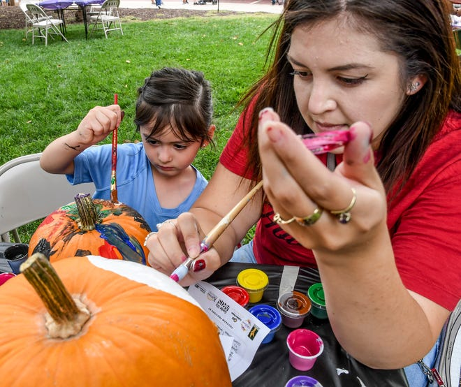 Lauren Peebles, 3, left, and Treana Rodelas get in the Halloween spirit Saturday by painting pumpkins in Stevens Park.  The pair were among 240 registered pariticipants in a pumpkin painting afternoon by Garden City Arts. Downtown Vision also had several games available for children to play as well as the Garden City Fire Department having a fire truck on hand for participants to check out and climb into the cab.