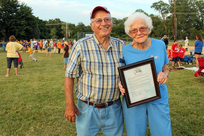 """The late Darrell and Jeanne Alleman pose on the baseball field they built on their farm near Granville with a proclamation, which acknowledged it as an Illinois Dream Field, recognized by the official """"Field of Dreams"""" movie site in Dyersville, Iowa."""