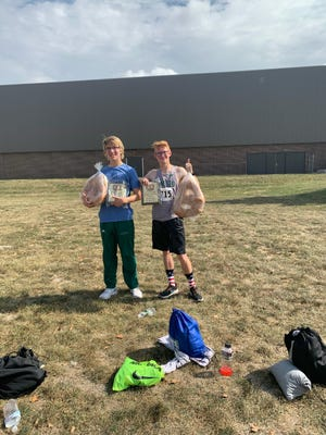 Gavin Allison, left; and Justin Johnson, two of the medalists at the Freeport Invitational Cross Country Meet, show the giant pretzels they were given for placing in the top five at the meet. Geneseo won the meet in a field of 20 teams.