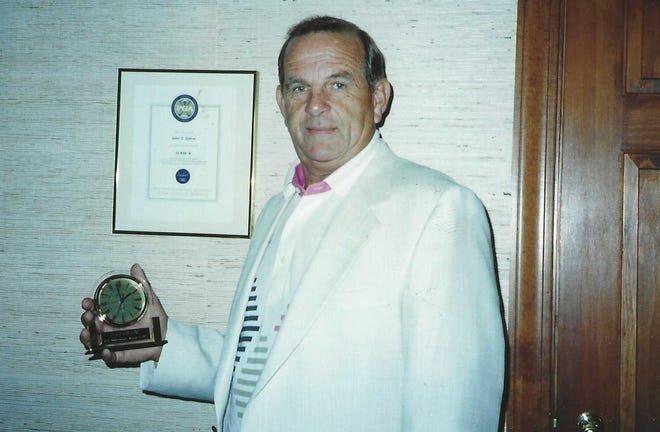 """Former Hendersonville Country Club head professional John """"Cliff"""" Collins poses with one of the awards he received. He passed away Thursday at the age of 87."""