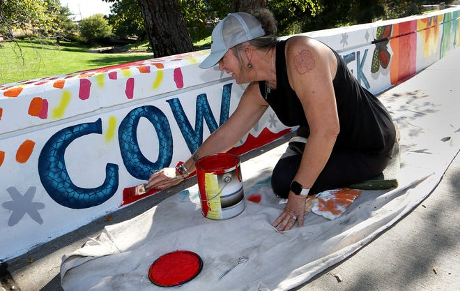 Artist Vickie Hoskins, who lives in Texas now but was born and raised in Hutchinson, paints a mural Friday, Oct. 8, 2021, along the wall next to Cow Creek in Avenue A Park.