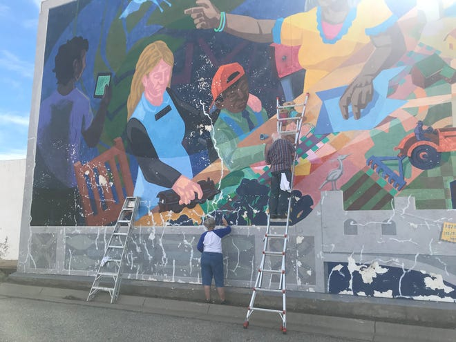 """October 9 volunteers began calking and sealing """"The Imagineers"""" mural, the first step in restoring a nearly 12 year old mural in downtown."""