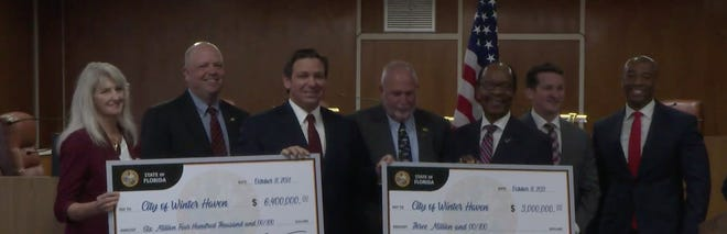 Gov. Ron DeSantis presents the Winter Haven City Commission with checks representing $9.4 million in funding for Logistics Parkway road improvements and fiber-optic network expansion.