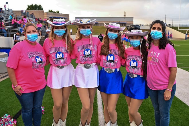 Dr. Katrina Birdwell (breast surgeon), Melissa Seale (Radiology director at Methodist Midlothian) and Midlothian High School Pantherettes pose for a photo before the Panthers' Pink Out game.