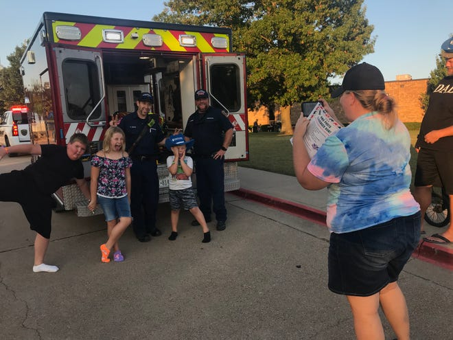 Midlothian paramedics Andrew Gatlin and Brandon Rogers pose with kids for a photo at T.E. Baxter Elementary during Midlothian's National Night Out on Tuesday, Oct. 5.