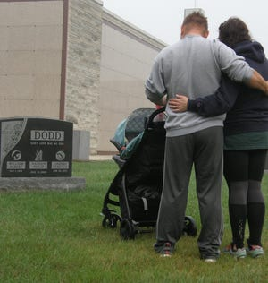 Monroe residents Will and Lindsay Dodd, with their three-month-old daughter, Theodora Elyse, stop to pray for their son, Nathan Philip. The Dodds gathered at St. Joseph Cemetery for the annual Memorial Walk.
