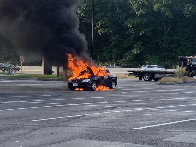 A car caught on fire late Monday afternoon at the Mass Pike's eastbound service plaza in Natick.