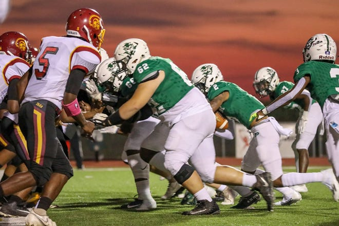 Plaquemine quarterback Mike Mitchell (2) carries for the Green Devils while teammates Carson Weber (62), Corey Thomas (66), Rickey Green (27) and Shermar Carter battle Tara under the autumn sky Friday night at Andrew Canova Green Devil Stadium. PHS routed the Trojans, 51-6, for their first win of the season.