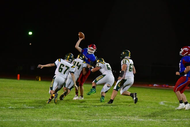 Greenback defense swarms the Hugoton High School quarterback in a play that didn't end well for the blue, and a game that went Pratt's way 44-7 on Friday in Hugoton.