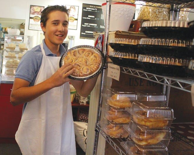 Elliott Wolf holds up a customer favorite - fresh, homemade cinnamon rolls - sold by the dozens at the Family Food Store on Thursdays, Fridays and Saturdays in Sawyer.