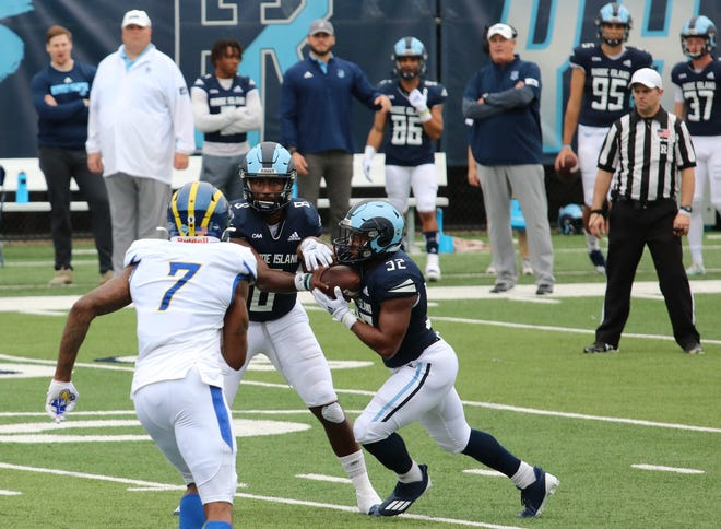 URI running back Justice Antrum takes the handoff from quarterback Kasim Hill as Delaware's Dae'Lun Darien closes in on Saturday afternoon at Meade Stadium. URI upset the No. 9 ranked Blue Hens are climbed to No. 12 in the latest FCS poll.