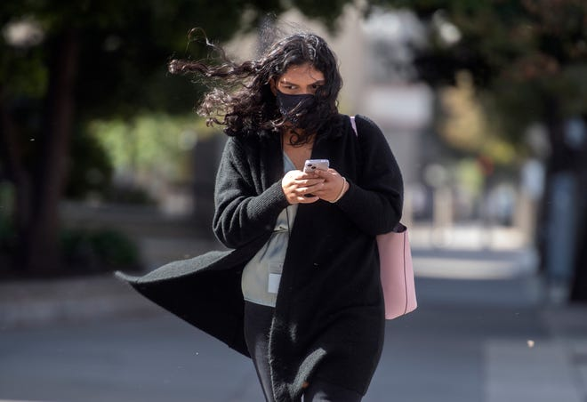 Strong winds buffet Ducle Piceno as she crosses San Joaquin Street at Weber Avenue in downtown Stockton.