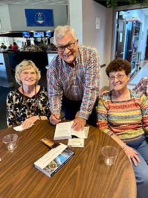 Author Randy Overbeck signs copies of his newly published novel for Portage County Retired Teachers members Phyllis Spangler, left,  and Adele Fussner.