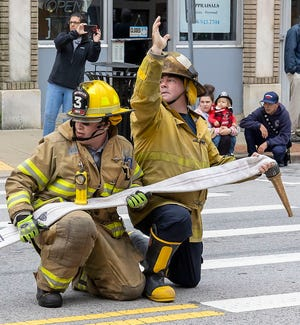 Firefighters signal to charge the line with water during a competition on Main Street in Webster on Sunday. The event was part of a muster and parade held to celebrate the 175th anniversary of the Webster Fire Department.