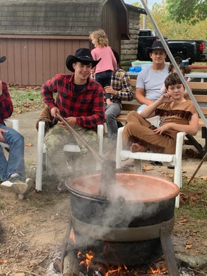 John Zook, 18, stirs the large kettle of apple butter.