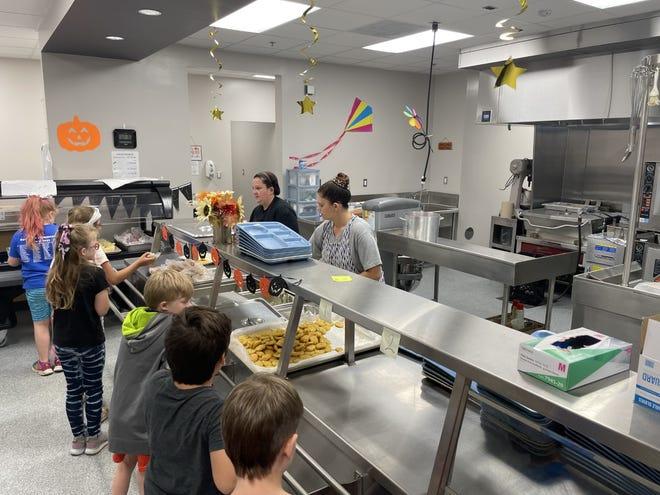 Cafeteria workers serve elementary students in the Van Buren School District lunch.