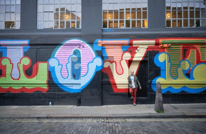 """Ben Eine, a celebrated street artist, is seen with his """"Love Love Love"""" mural, painted on Ebor Street in East London. Eine will begin work on a new, original mural at 1000 Garrison Ave. on Oct. 16."""