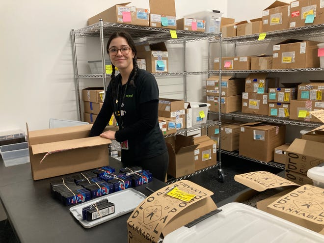 Julia Brito breaks down products into the safe vault of ReLeaf Alternative, Mansfield's first marijuana dispensary.