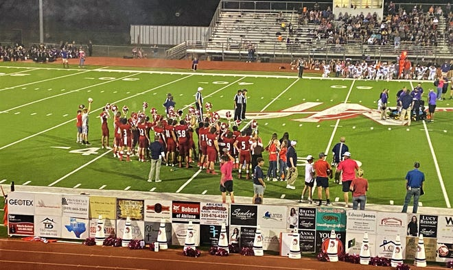 Jim Ned players raise their helmets to support injured Early quarterback Jaxyn Price, who was taken from the Indian Stadium field on a stretcher Friday. Oct. 8 2021