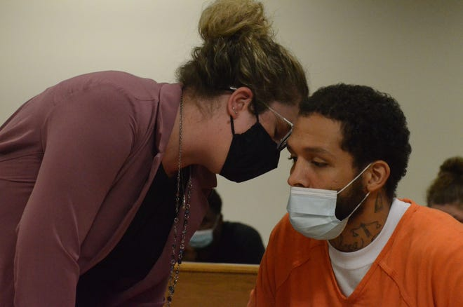 Attorney Kim Wickham leans in to speak with her client, Lansing Hodges, during a Monday preliminary hearing.