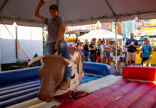 Kyle Buchwalter, 16 of Pickerington, hangs on with one hand as he rides the mechanical bull ride on the first day of the Fairfield County Fair in Lancaster Ohio on October 10, 2021.