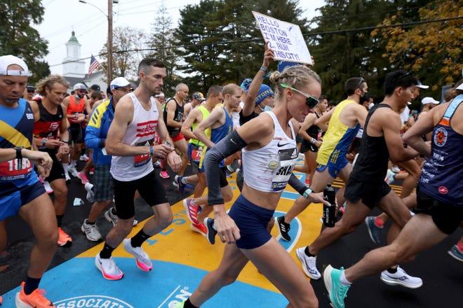 Runners cross the start line of the 125th Boston Marathon, Monday, Oct. 11, 2021, in Hopkinton, Mass.
