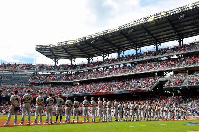 The Brewers stand for the national anthem Monday before game 3 of their series with the Braves. The game could have been pushed until late afternoon, which would have created challenging shadows.