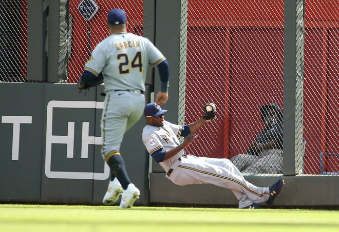 The ball pops out of the glove of Brewers center fielder Lorenzo Cain after he ran into the wall trying to make a catch on what turned into a triple by the Braves' Adam Duvall on Monday.
