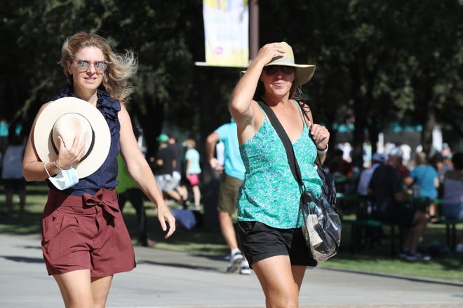 Hollie Schaefer, left, and Hally Cohen, both of Santa Monica, hold their hats as strong winds blow at the Indian Wells Tennis Garden during the BNP Paribas Open in Indian Wells, Calif., on October 11, 2021.