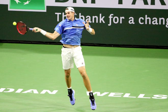 American John Isner returns a shot to Yoshihito Nishioka of Japan during the BNP Paribas Open in Indian Wells, Calif., on October 10, 2021.