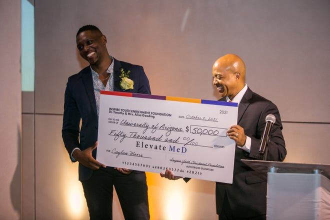 University of Arizona medical student Caylan Moore receives a $50,000 award from the Inspire Youth Enrichment Foundation, presented to him by ElevateMeD co-founder Greg Umphrey, M.D., on Oct. 2, 2021.