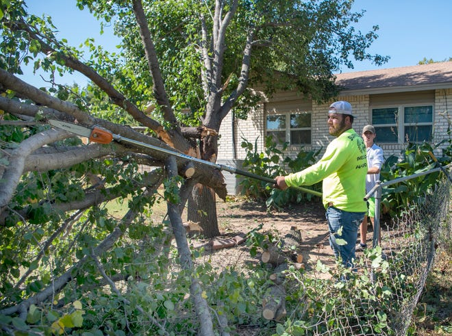 Workers clear debris left by severe thunderstorms Sunday night.