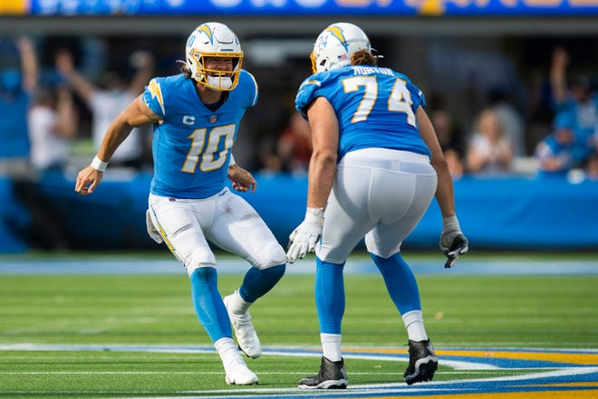 Los Angeles Chargers quarterback Justin Herbert (10) celebrates his touchdown pass with offensive tackle Storm Norton (74) during an NFL football game against the Cleveland Browns Sunday, Oct. 10, 2021, in Inglewood, Calif.