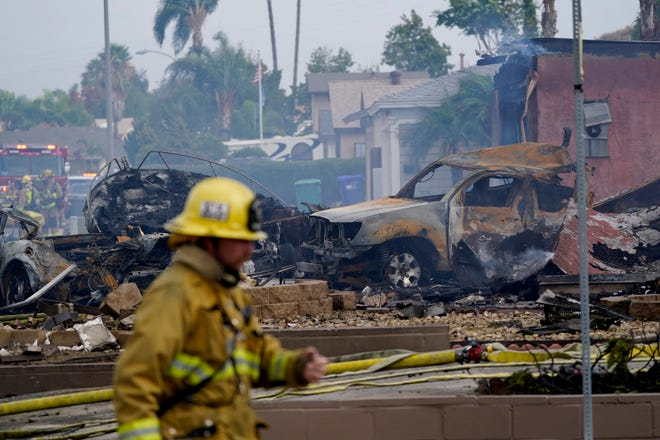 Fire crews work the scene of a small plane crash, Monday, Oct. 11, 2021, in Santee, Calif. At least two people were killed and two others were injured when the plane crashed into a suburban Southern California neighborhood, setting two homes ablaze, authorities said.