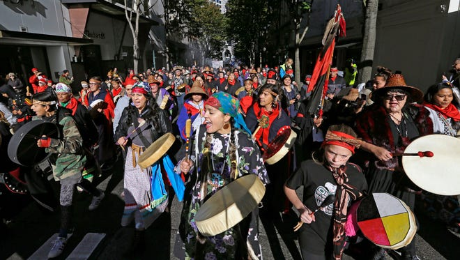 Drummers sing as they lead a march during an Indigenous Peoples Day event Monday, Oct. 9, 2017, in Seattle.