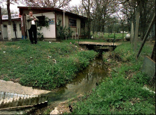 Several years ago Sergio Duron stands in front of his store in the Stony Point subdivision in Bastrop County and overlooks a small creek that runs through his property. Inadequate drainage often leaves his land flooded, which includes his septic drain field.