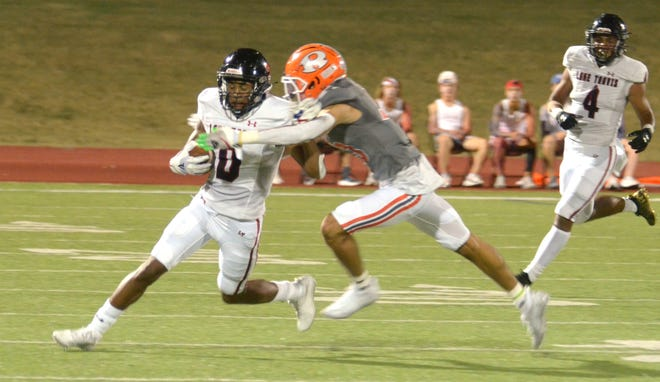 Lake Travis senior receiver Caleb Burton tries to break a tackle by Rockwall's Cadien Robinson in a nondistrict game last month. Burton, a five-star recruit pledged to Ohio State, played at Del Valle earlier in his high school career before joining the Lake Travis program after his father, former Del Valle head coach Charles Burton, joined the Lake Travis coaching staff. The Cavs host Del Valle Friday.