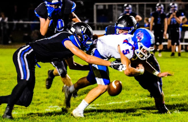 Colo-NESCO's Andrew Tschantz (31) and Kaleb Gray force BGM's Jacob Maurer to fumble the football and it was later recovered by their teammate Nolan Smith during the Royals' 64-58 loss to BGM Friday at Colo.