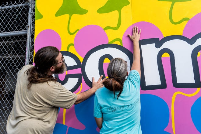 Chris Stevens and Amanda Percle-Stevens install the mural in downtown Houma Tuesday morning.