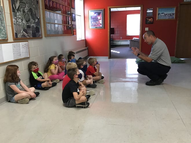 Firefighter Jim Perreault talks with Cathedral kindergartners