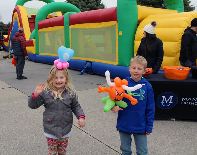 Lily and William Schroeder pose for a photo with their balloon animals during the 2019 Fall Festival in Grimes.